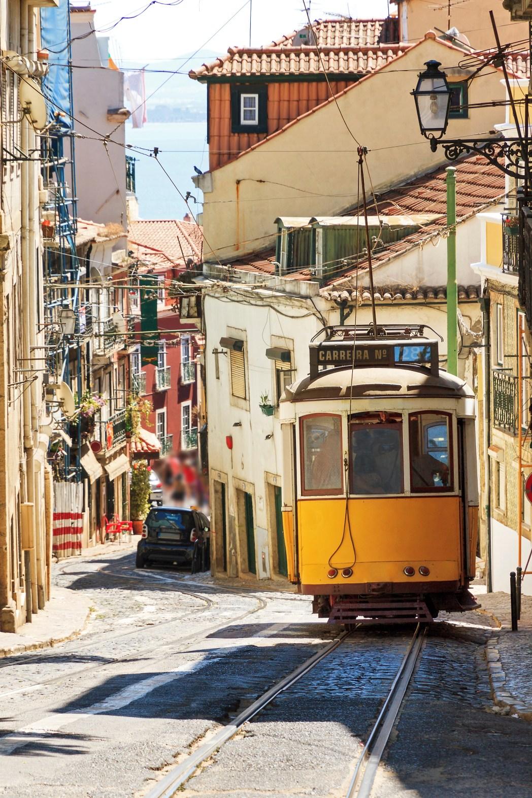 Κίτρινο τραμ ανεβαίνει σοκάκι της Λισαβόνας - οι καλύτεροι φθινοπωρινοί προορισμοί