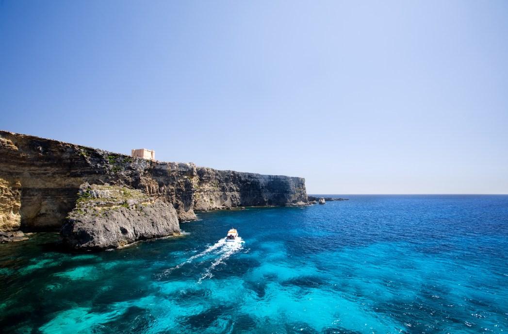 Ένα σκάφος διασχίζει τα βαθιά μπλε νερά της Μάλτας
